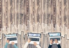 Top view of businesspeople sitting at table and using gadgets. Group of three people with devices in hands working together as symbol of networking and Stock Image