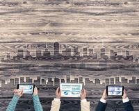 Top view of businesspeople sitting at table and using gadgets. Group of three people with devices in hands working together as symbol of networking and Stock Photography