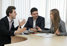 Group of three people having discussion. Office Interior Charts and Paperwork on Desk Business people tries to convince each other making eloquent gestures royalty free stock images