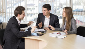 Group of three people having discussion. Office Interior Charts and Paperwork on Desk Business people tries to convince each other making eloquent gestures stock images