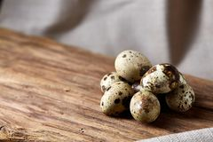 Group of three quail eggs on piece of wood over homespun tablecloth, top view, selective focus, backlight. Group of three spotted quail eggs on a piece of wood Stock Photos