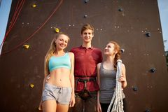 Group of three rock climbers with safety equipment smiling and looking at camera against artificial climbing wall. Climbing instructor with two girls Royalty Free Stock Photos