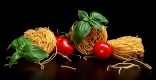 Group of three round balls of raw pasta on black Royalty Free Stock Image