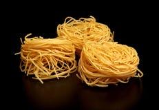 Group of three round balls of raw pasta on black Stock Photography