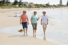 Group of three senior mature retired women on their 60s having fun enjoying together happy walking on the beach smiling playful royalty free stock images