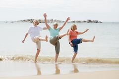 Group of three senior mature retired women on their 60s having fun enjoying together happy walking on the beach smiling playful. Lovely group of three senior stock image