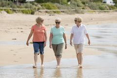 Group of three senior mature retired women on their 60s having fun enjoying together happy walking on the beach smiling playful Royalty Free Stock Photo