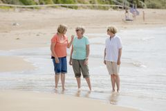 Group of three senior mature retired women on their 60s having fun enjoying together happy walking on the beach smiling playful Stock Photo