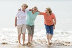 Group of three senior mature retired women on their 60s having fun enjoying together happy walking on the beach smiling playful Stock Photography