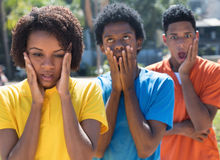 Group of three shocked african american young adults. Outdoor in the city in the summer Stock Photo