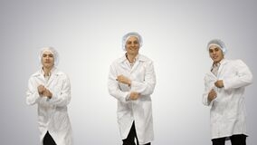 Group of three smiling doctors on gradient background.
