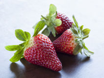 Group of three strawberries. Group of three strawberry with bright green leaves Stock Images