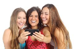 Group of three teenager girls laughing looking the smart phone. Isolated on a white background Stock Photos