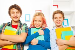 Group of three teens stand holding textbooks. Three cute teen kids with textbooks standing at home smiling and looking at home Stock Images