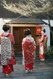 Three Geisha in a street of Kyoto. A group of three tourists dressed as geisha or maiko posing for photos in front of a Japanese house in Kyoto Royalty Free Stock Image