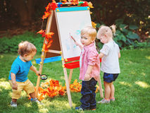 Group of three white Caucasian toddler children kids boys and girl standing outside in summer autumn park by drawing easel. With markers, playing studying stock photo