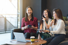 Group three women meeting in a coffee shop chatting to each othe. R while using smartphone tablet and laptop, internet of things conceptual Stock Photo