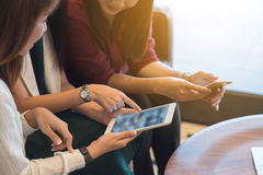 Group three women meeting in a coffee shop chatting to each othe. R while using smartphone tablet and laptop, internet of things conceptual Royalty Free Stock Photo