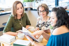 Female friends at book club. Group of three women sitting at table and reading books at club Royalty Free Stock Photos