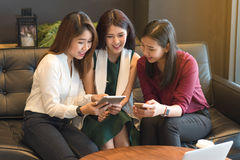 Group of three woman use tablet and laptop in coffee shop. Group of three women use tablet and laptop in coffee shop together Royalty Free Stock Photos
