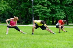 Group of three young athletes doing stretching exercise Stock Images