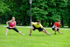 Group of three young athletes doing stretching exercise Royalty Free Stock Photography