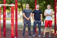 Positive sports men friends on a blurred park background. Comfortable sportswear concept. A group of three young athletes posing on a blurred training area Stock Photo
