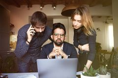 Group of three young coworkers working at modern place on mobile laptop computer on wooden table. Horizontal, blurred royalty free stock photography