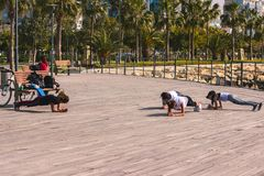 Group of three young friends doing a plank on exercise at front of pier stock photos