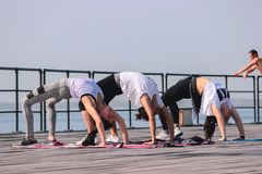 Group of three young friends doing a plank on exercise at front of sea royalty free stock photography