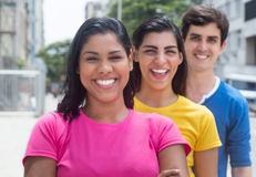 Group of three young people in colorful shirts standing in line. In the city outside on an summer day with streets, buildings and trees in the background Stock Photos