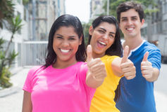 Group of three young people in colorful shirts standing in line and showing thumbs. In the city outside on an summer day with streets, buildings and trees in Royalty Free Stock Photos