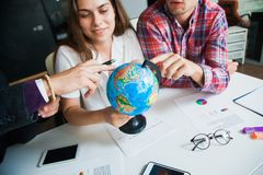 Group of three young people with globe choose country to travel to. Stock Photo