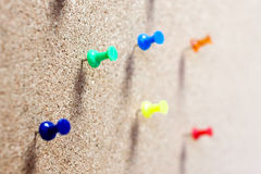 Group of thumbtacks pinned on corkboard. Stock Photography