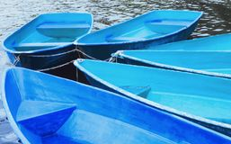 Blue Recreation Boats. Group of tied blue and turquoise recreation rowing boats on the water closeup. Soft selective focus Royalty Free Stock Image