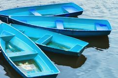 Blue Recreation Boats On The Water. Group of tied blue and turquoise recreation rowing boats on the water. Soft selective focus Royalty Free Stock Photo