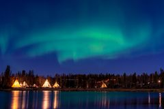 Group of Tipi under Aurora Borealis with smooth water reflection royalty free stock image