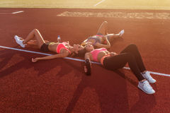 Group of tired fit girls lying on stadiun in circle outdoors Stock Photos