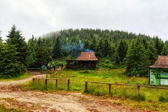Group of tired tourists near the resting house in Carpathian mountains, rain weather Stock Photo