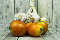 Group of tomato and garlic on wooden plank Stock Photo