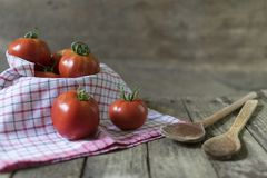 Group of tomatoes in basket with dishcloth and wodden spoons on Stock Photography