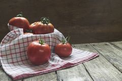 Group of tomatoes in basket with dishcloth on wooden table Royalty Free Stock Images