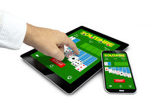 Group of touchscreen devices with solitaire app and a finger tou Stock Photo