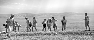 A group of tourist following christ holy ground, at the sea of Galilee. Royalty Free Stock Photography