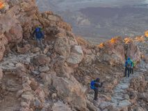 Group of tourist hikers walking from sun rise on steep footpath royalty free stock photos