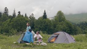 Group of tourist people resting in campsite while summer hiking in mountain stock video