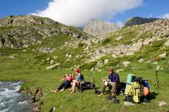 Group of tourist relaxing on the stream bank Stock Image