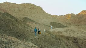 Group of tourist walk along the rock canyon in hot desert, tourists take picture and have fun. Desert mountains