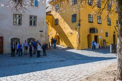 Group of tourists admiring the colorful medieval streets, the yellow house is the birtplace of Vlad Tepes also known as Dracula. royalty free stock photos