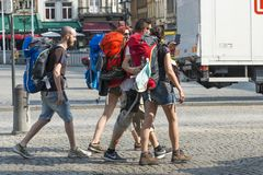 A group of tourists backpacking. BRUGES, BELGIUM - JULY 3, 2015: A group of tourists backpacking, roam the streets of the historic center of the city royalty free stock photo